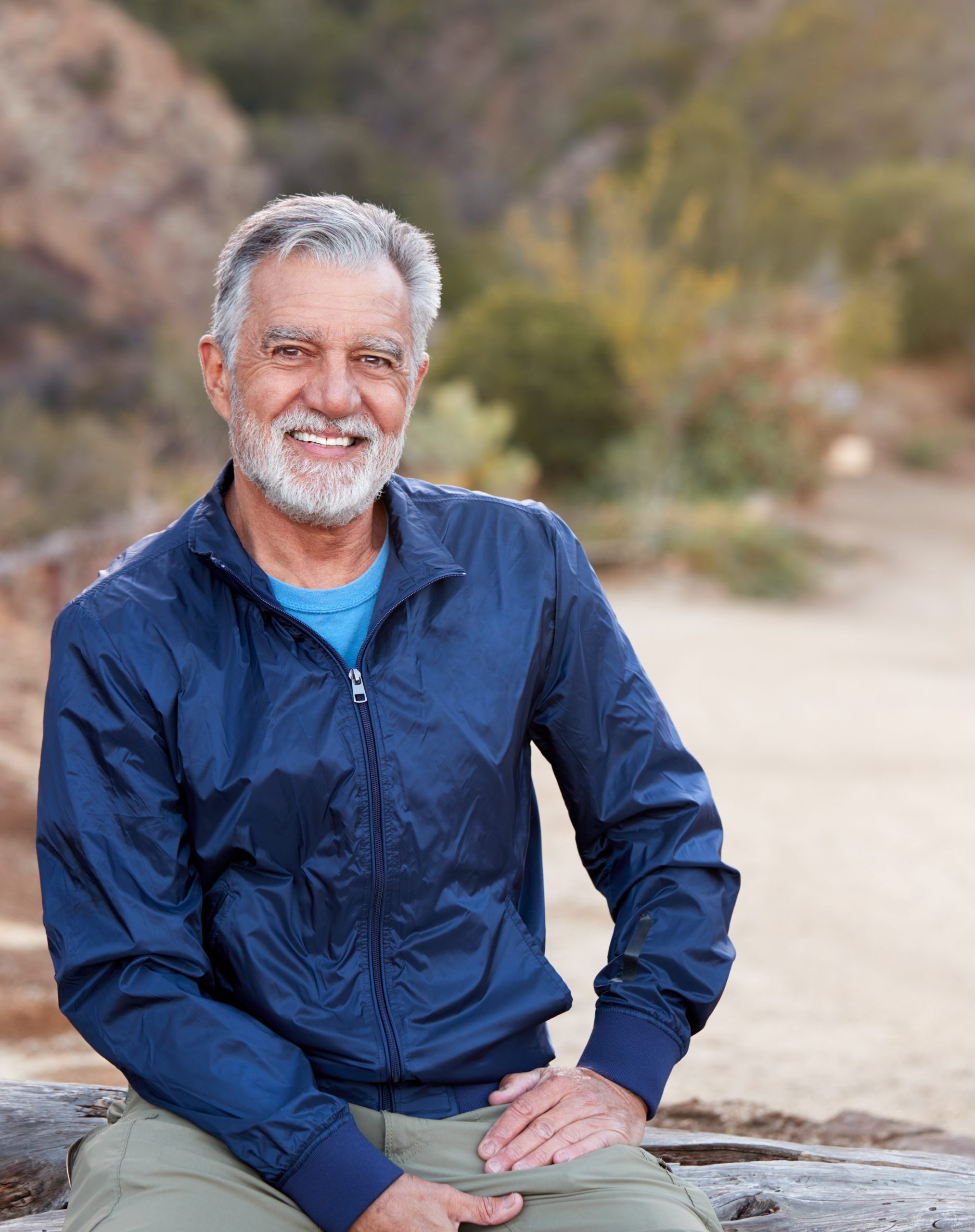 Portrait Of Smiling Hispanic Senior Man Outdoors In Countryside
